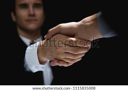 Business partners making handshake in dark shadow Stockfoto ©