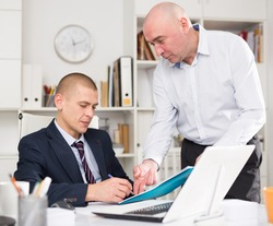 Business partners men working in the office, make a joint business project, discuss the nuances
