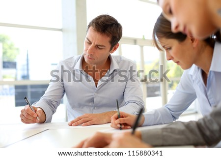 Business partners signing contractual documents