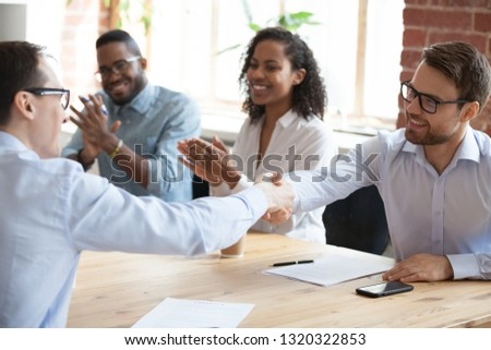 Business partners sitting at desk in boardroom, representatives shaking hands express respect and gratitude with hand gesture. Company executives reach agreement feels satisfied after signing contract #1320322853