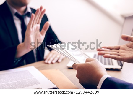 Business partners submit fraudulent cash to entrepreneurs whose male businessmen refuse to accept bribes in the office. Stock photo ©
