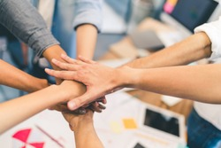 Business partners teamwork or friendship concept. Multi-ethnic diverse group of colleagues join hands together. Creative team, coworkers, or college students in project meeting at modern office