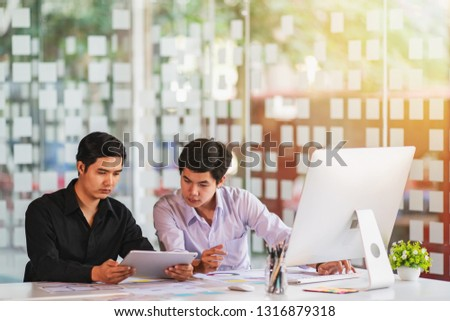 Business partners use tablet discussing documents and ideas at meeting.