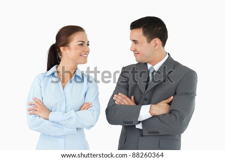 Business partners with arms folded looking at each other against a white background