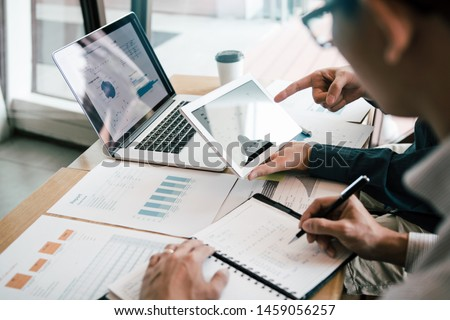 Business partnership coworkers using a tablet to analysis graph company financial budget report and cost work progress and planning for future in office room.