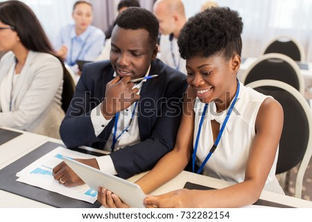 business, people and education concept - african american businessman and businesswoman with tablet pc computer at international conference #732282154
