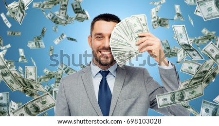 business, people and finances concept - smiling businessman with bundle of american dollar cash money over blue background #698103028