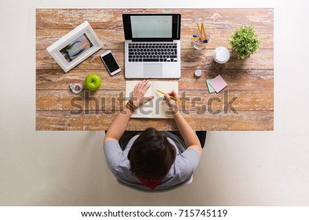 business, people and freelance concept - woman with laptop computer drawing to notebook at home or office table #715745119