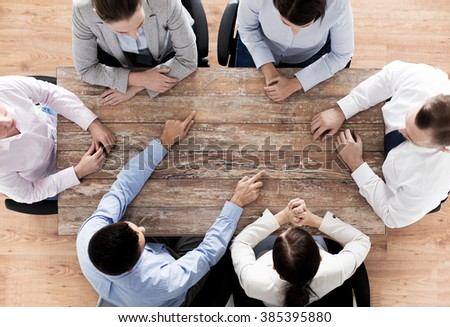 business, people and team work concept - close up of creative team sitting at table and pointing finger to something in office #385395880