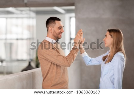 business, people and teamwork concept - happy smiling businesswoman and businessman making high five at office #1063060169