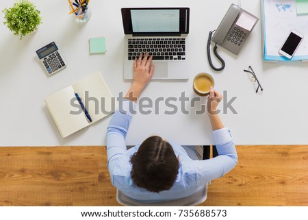 business, people and technology concept - businesswoman with laptop computer working at office and drinking coffee #735688573