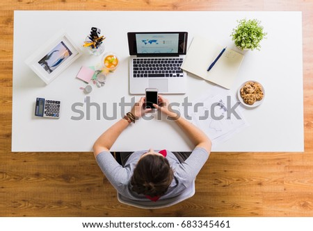 business, people and technology concept - woman with smartphone and laptop at office table #683345461