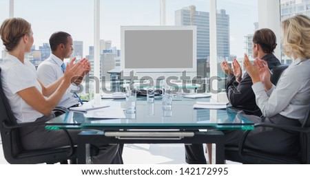 Business people applauding during a video conference in the boardroom