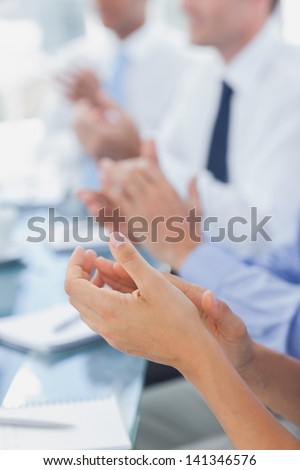 Business people applauding together during a meeting