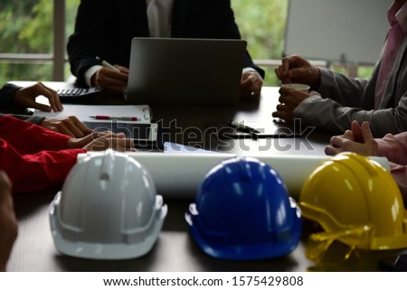 Business people are discussing in the meeting room with laptop, computer device, calculator and papers. With engineer helmets as blurred foreground.
