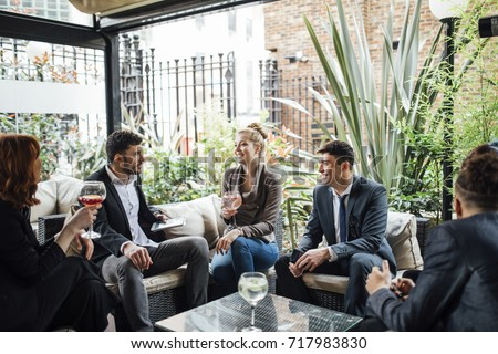 Business people are having a meeting after work in a bar courtyard, enjoying cocktails while looking at statistics on technology.