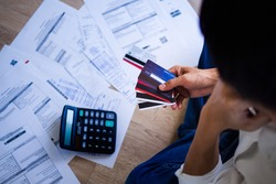 Business people are stressed about credit card debt and many bills on the floor. Men get trouble by calculating monthly expenses and then budgeting not enough money for paying debts.
