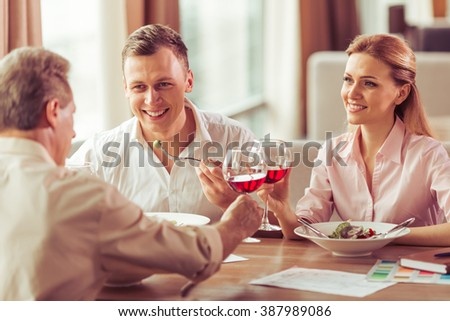 Business people are talking and smiling during business lunch at the restaurant. Man and woman are clanging glasses of wine together