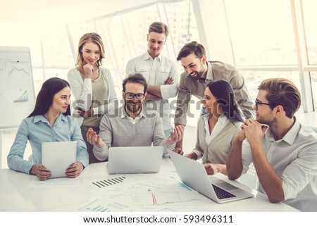 Business people are using gadgets, discussing documents and smiling during the conference #593496311