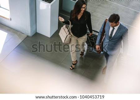 Business people arriving at hotel with luggage. Business people with luggage walking together and chatting.