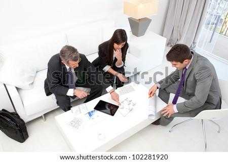 Business people at financial meeting with documents and tablet on table. - stock photo