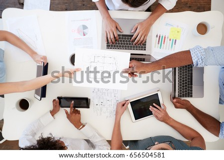 Business people at meeting passing document, overhead shot #656504581