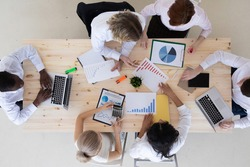 Business people brainstorming at office desk analyzing financial reports and pointing out financial data on a sheet, top view