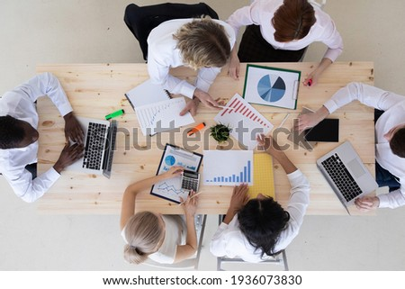 Business people brainstorming at office desk analyzing financial reports and pointing out financial data on a sheet, top view Zdjęcia stock ©