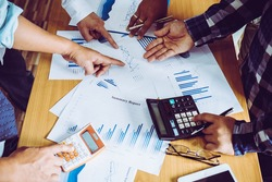 Business people brainstorming at office desk, they are analyzing financial reports and pointing out financial data on a sheet
