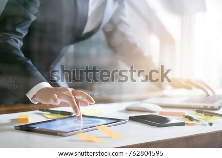 Business people busy working the charts and graphs showing in the tablet and laptop of successful in office background #762804595