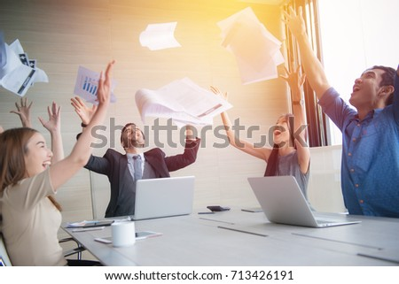 business people celebrating by throwing documents after working success in office. #713426191