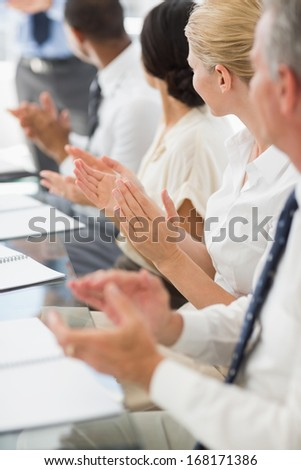 Business people clapping colleague at a meeting in the office
