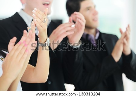 Business people clapping hands during meeting at office or presentation