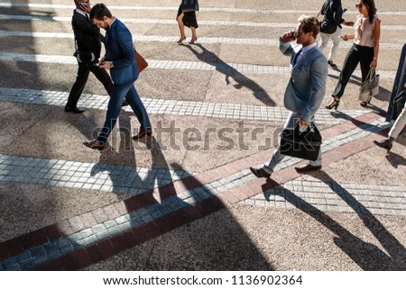 Business people commuting to office in the morning carrying office bags and using mobile phones. #1136902364