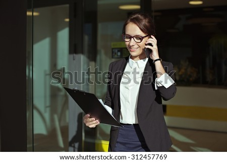 Photo of Business people concept- image of a business woman who goes out of office, talking on the phone with the documents in the hands. Beautiful business lady manager with documents.