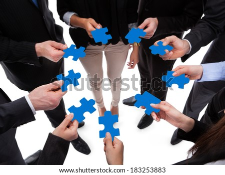 Business people connecting puzzle pieces over white background