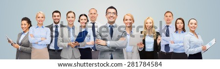 business, people, corporate, teamwork and office concept - group of happy businesspeople over blue background