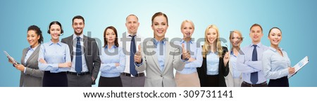 business, people, corporate, teamwork and office concept - group of happy businesspeople showing thumbs up over blue background