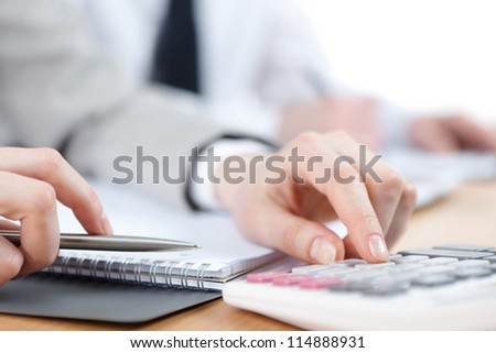 Business people counting on calculator sitting at the table. Close up view of hands and stationery