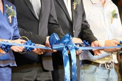 Business people cutting blue ribbon scissors in hands, store grand opening ceremony.