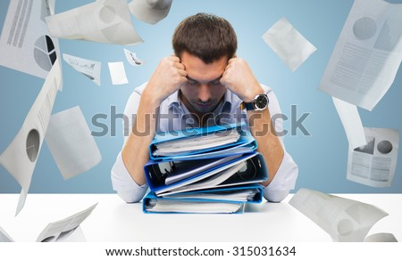business, people, deadline, stress and paperwork concept - sad businessman with stack of folders and falling papers over blue background