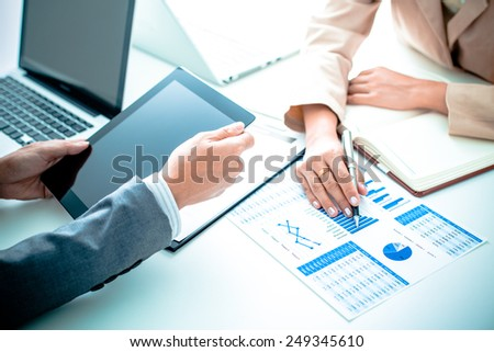Business people discussing the charts and graphs showing the results of their successful teamwork #249345610