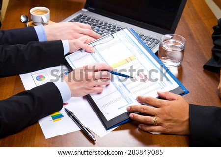 Business people discussing the charts and graphs showing the results of their successful teamwork #283849085