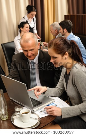 Business people discussion woman point laptop at restaurant conference room