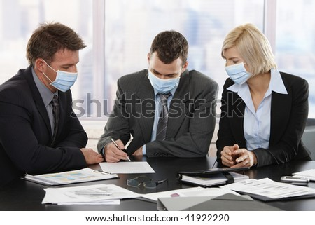 Business people fearing h1n1 swine flu virus wearing protective face mask during meeting at office.