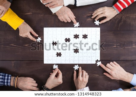 Business people finding solution together at office. Jigsaw puzzle and searching solutions concept.