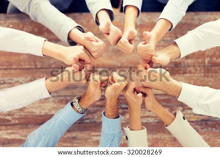 business, people, gesture and team work concept - close up of creative team showing thumbs up and sitting at table in office #320028269