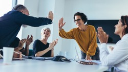 Business people giving each other high five and clapping. Business team celebrating success.