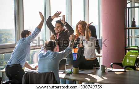 Business people giving five after dealing and signing contract or agreement with partners abroad. Colleagues showing team work in office interior.