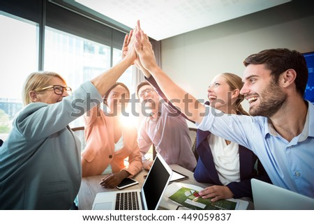 Business people giving high five at desk in the office stock photo